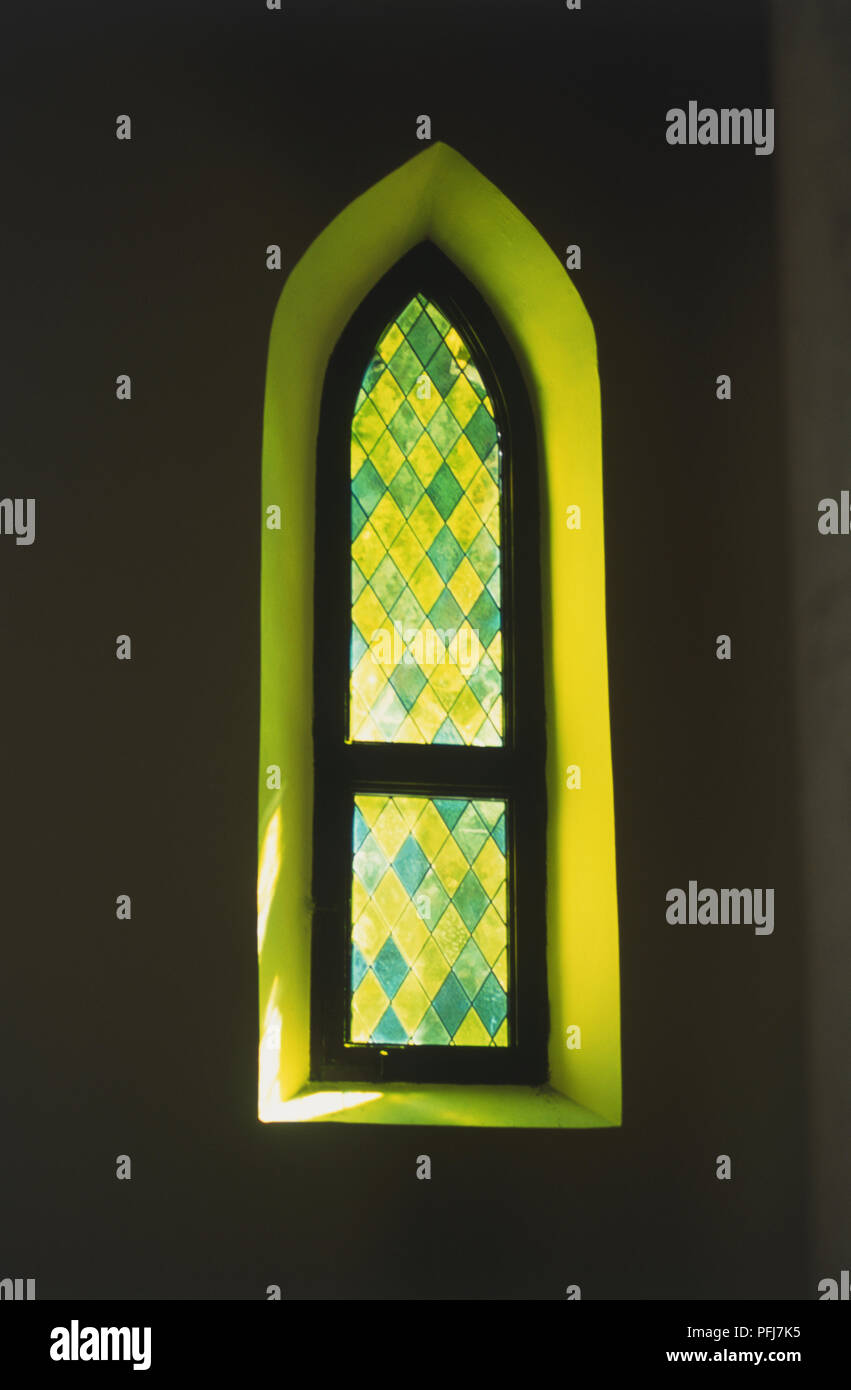 Oval window, set in thick wall, light coming through lozenge shaped stained glass - Stock Image
