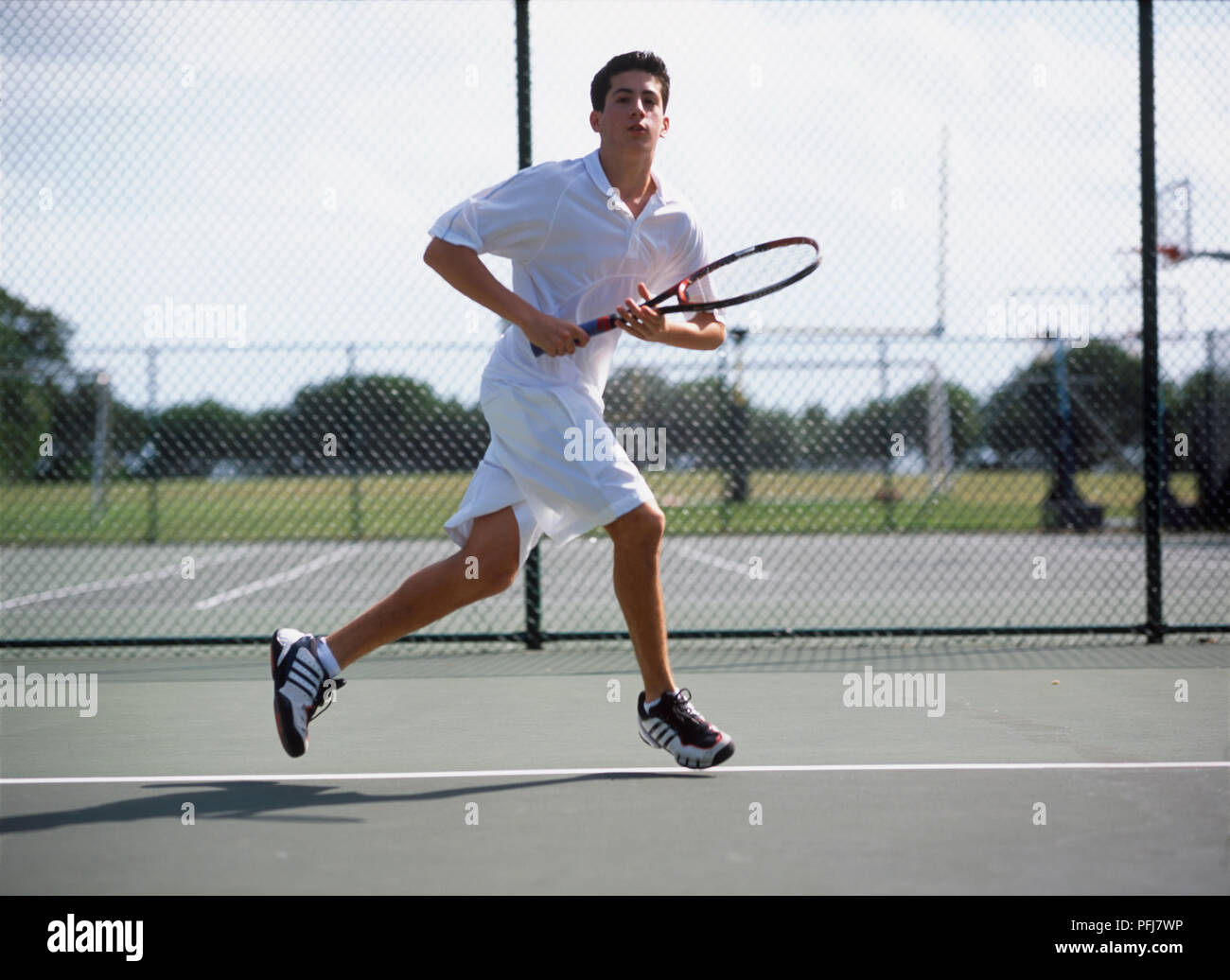 Boy In White Tennis Clothes Running Across Tennis Court Holding Tennis Racket Lightly In Both Hands Stock Photo Alamy