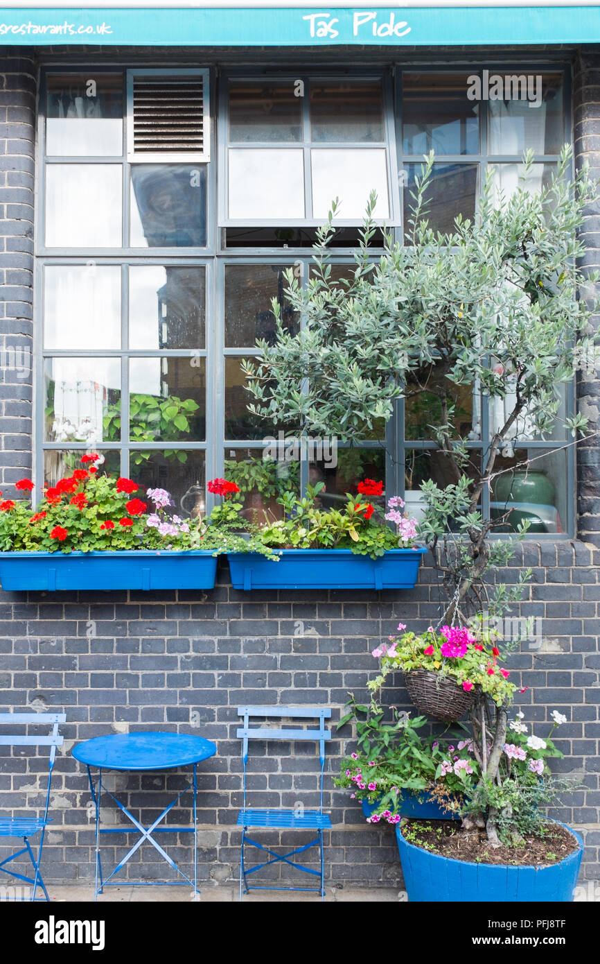 Bright blue tables and chairs outside Tas Pide Turkish mezze restaurant in New Globe Walk by the Shakespeare Globe Theatre - Stock Image