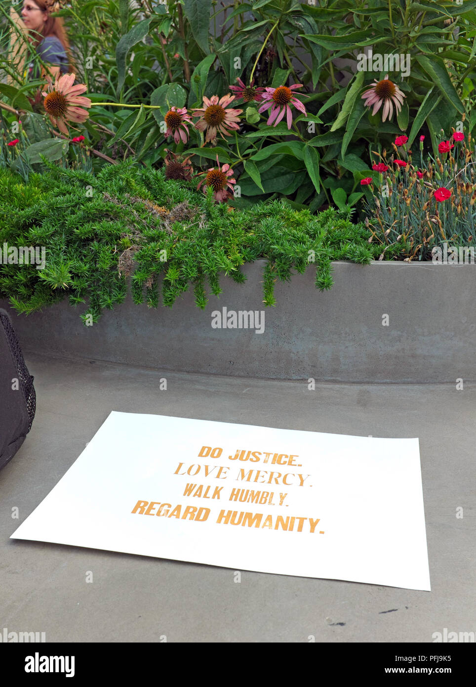 A sign left on a public seating area in Freedom Park in Washington DC stating- Do Justice, Love Mercy, Walk Humbly, and Regard Humanity. - Stock Image