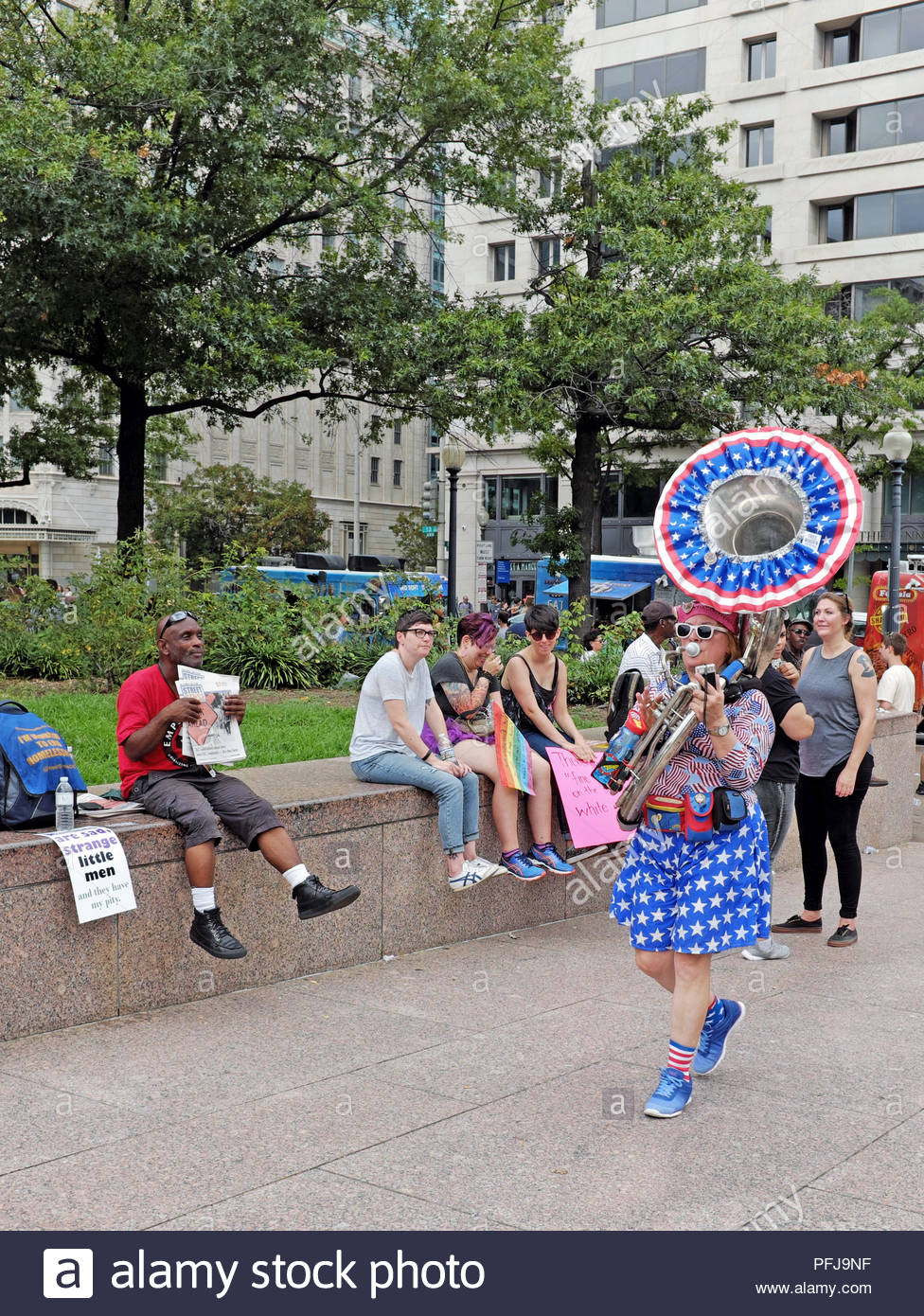 A female tuba player dressed in patriotic clothing makes her way through Freedom Park in Washington DC during an anti-hate rally on August 19, 2018. - Stock Image