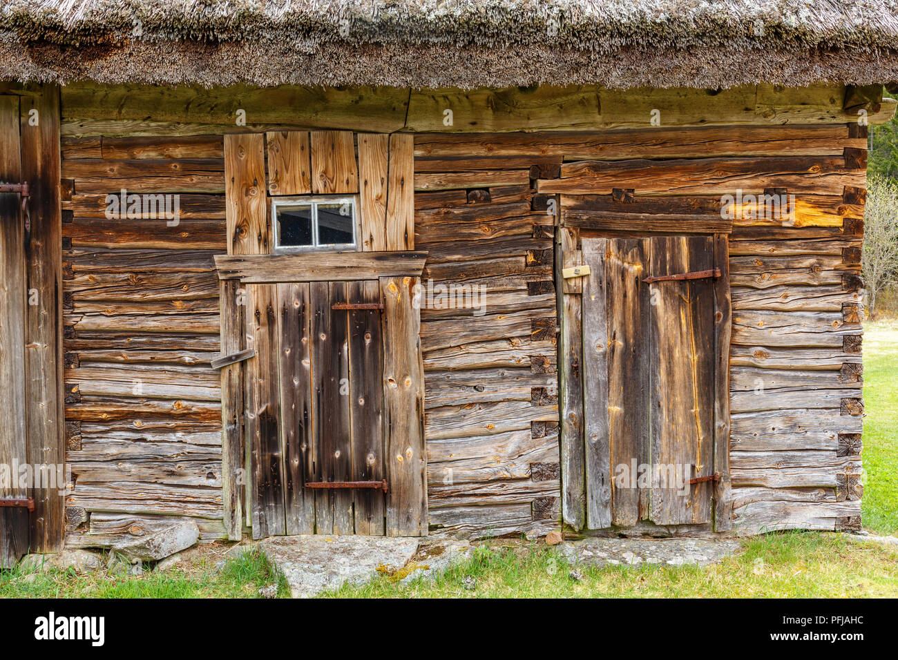 Doors on an old log barn with a thatched roof - Stock Image