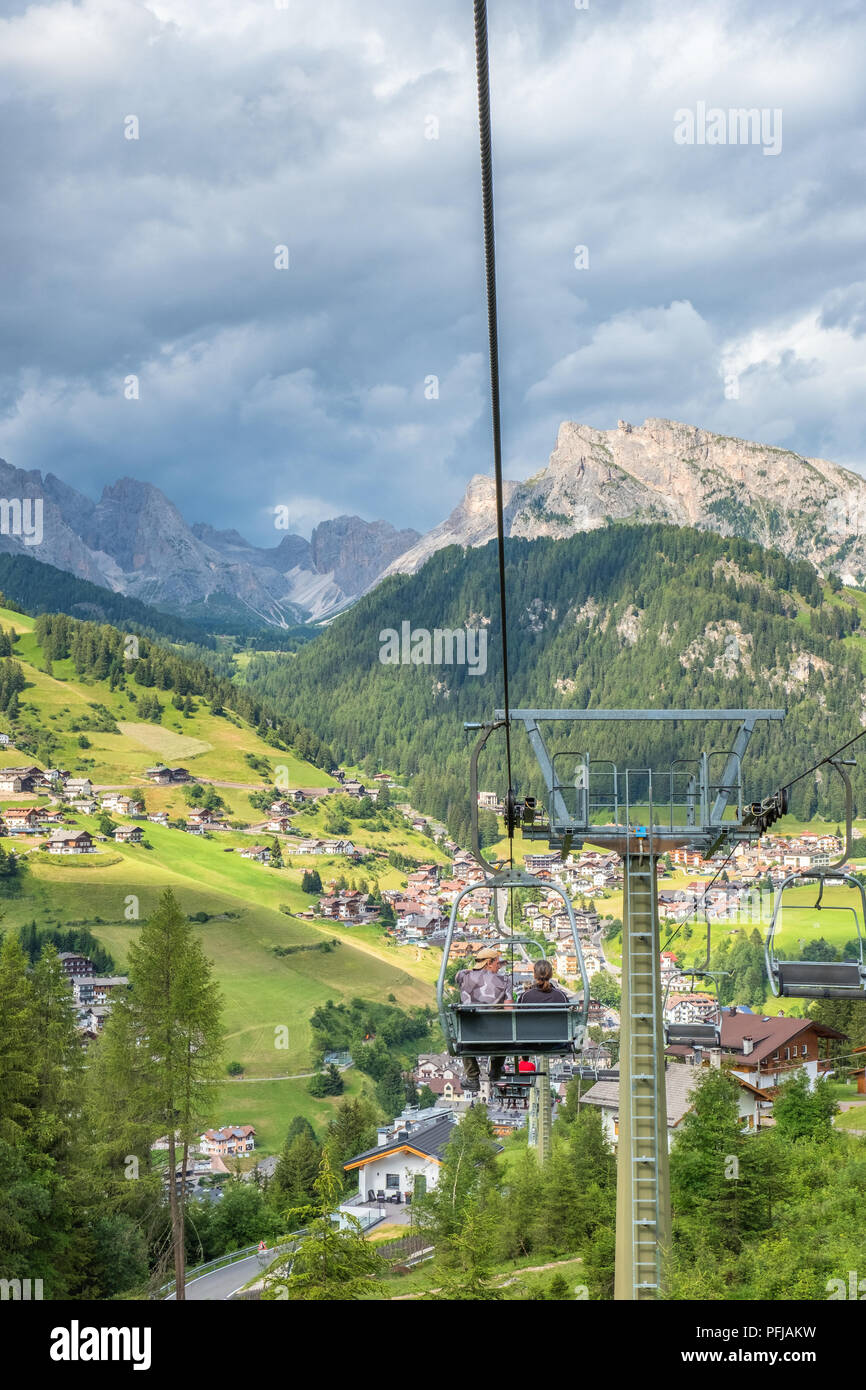 People in a chair lifts down to Santa Cristina in val gardena, Italy Stock Photo