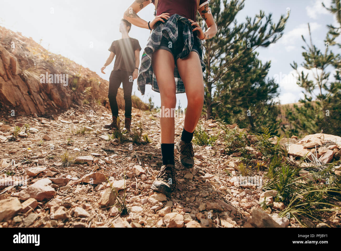 Explorer couple walking in a forest. Woman walking on a rocky path with her partner following her on a sunny day. - Stock Image