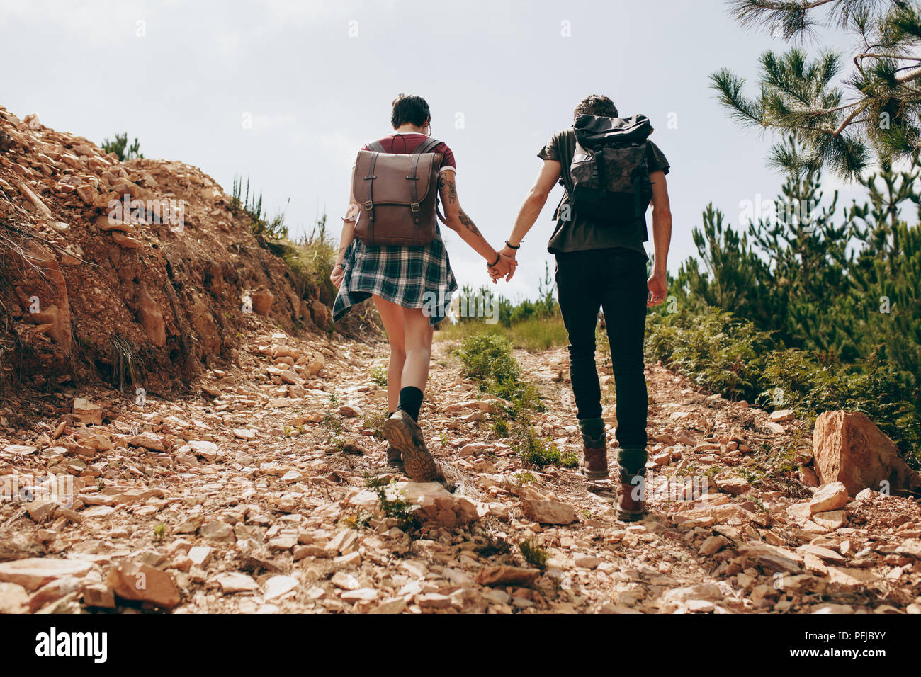 Rear view of a man and woman trekking a rough terrain together holding hands. Couple wearing backpacks on a holiday hiking on a hill. - Stock Image