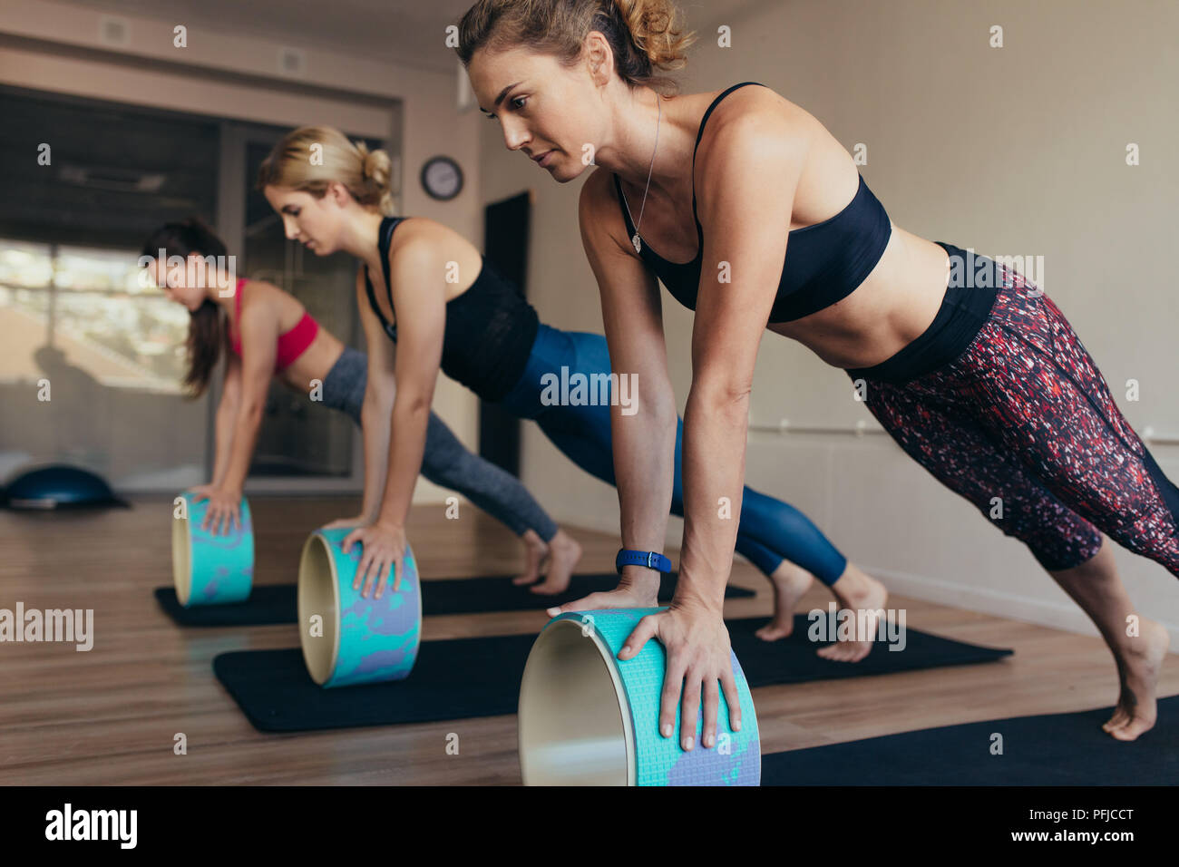 Women in push up position resting their hands on yoga wheel doing pilates workout. Three women doing pilates workout at the gym. - Stock Image