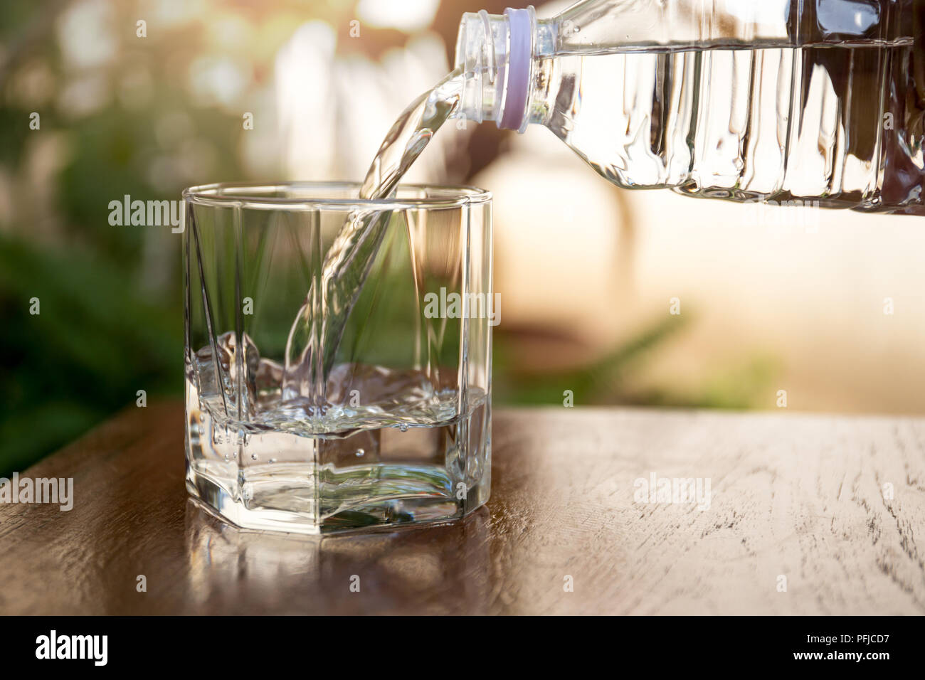 Outstanding Pouring Fresh Water From Bottle On Glass On Wooden Table Interior Design Ideas Inesswwsoteloinfo
