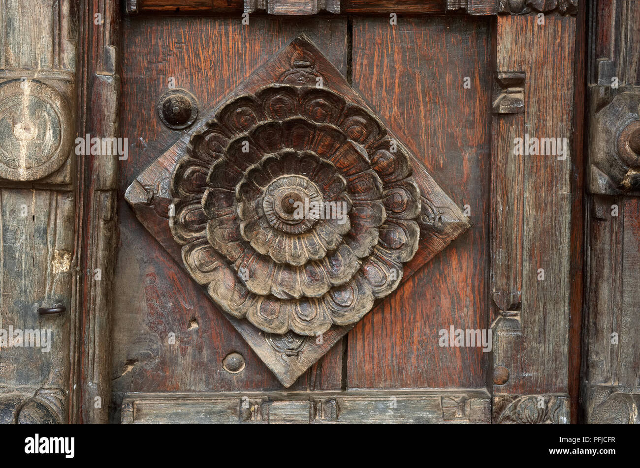 India, Tamil Nadu, Padmanabhapuram, royal palace, woodwork on main gate showing stylised lotus motif, close-up - Stock Image