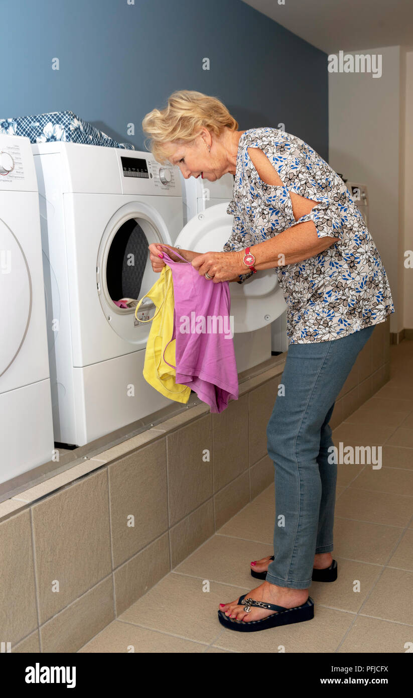 Elderly woamn removing dried clothing from a drier machine in a laundry room Stock Photo