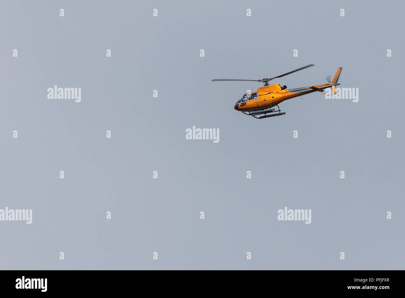 Helicopter flying over shoreham by sea coastal area. Image taken with 150-600 sigma lens while photographing waders. Vertical lift off and hovering. - Stock Image