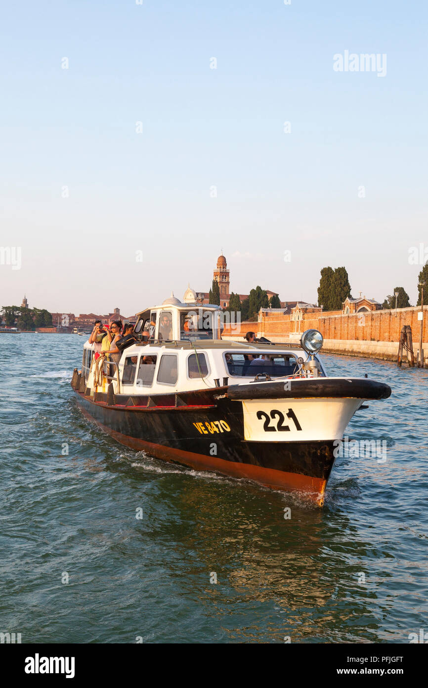 Close up front view of a vaporetto waterbus, water bus, Venice, Veneto, Italy passing San Michele Island at sunset full of people tourists. Public tra - Stock Image