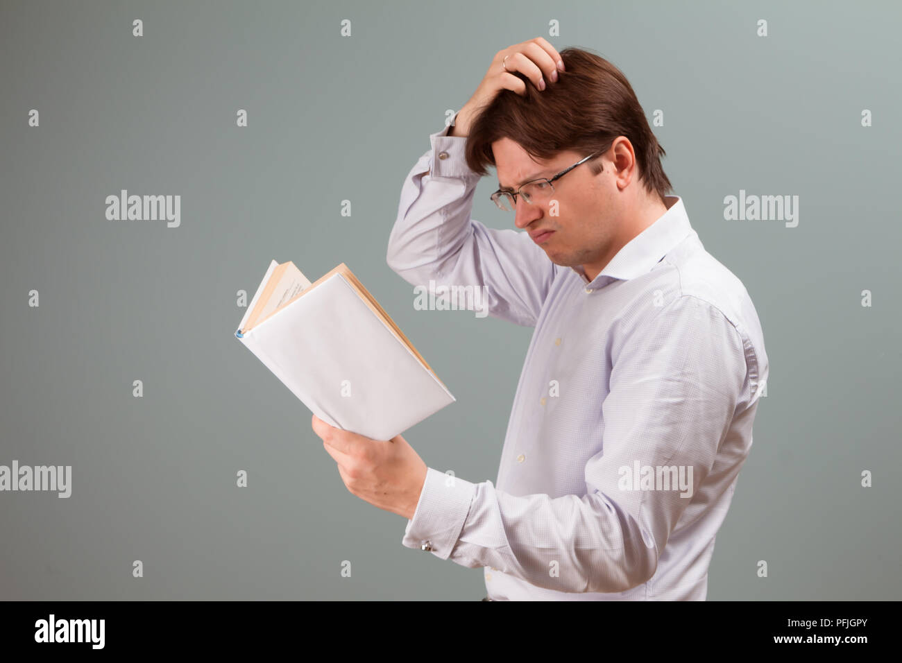 A young man, focused on reading a book in white cover, with confused emotion on the face, scratches his head; horizontal orientation studio portrait. - Stock Image