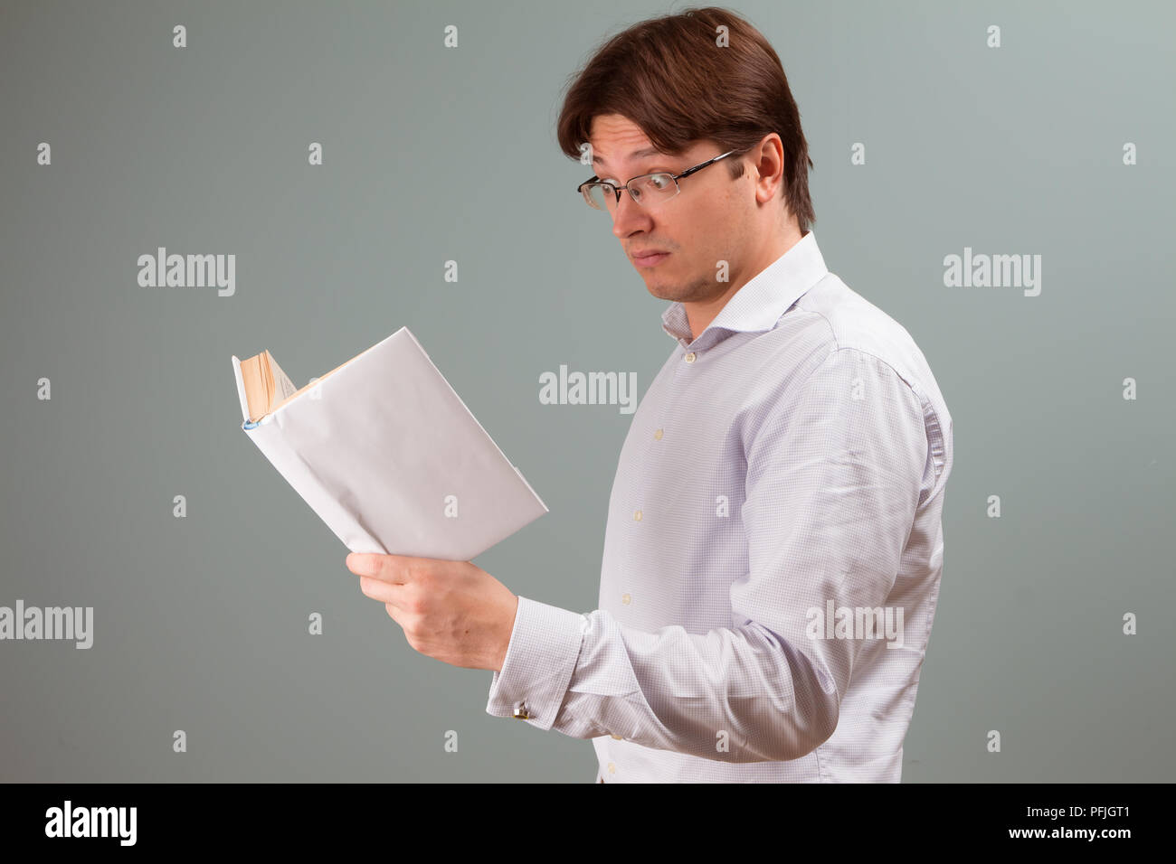 A young man, focused on reading a book in white cover, with surprised emotion on the face; horizontal orientation studio portrait. - Stock Image