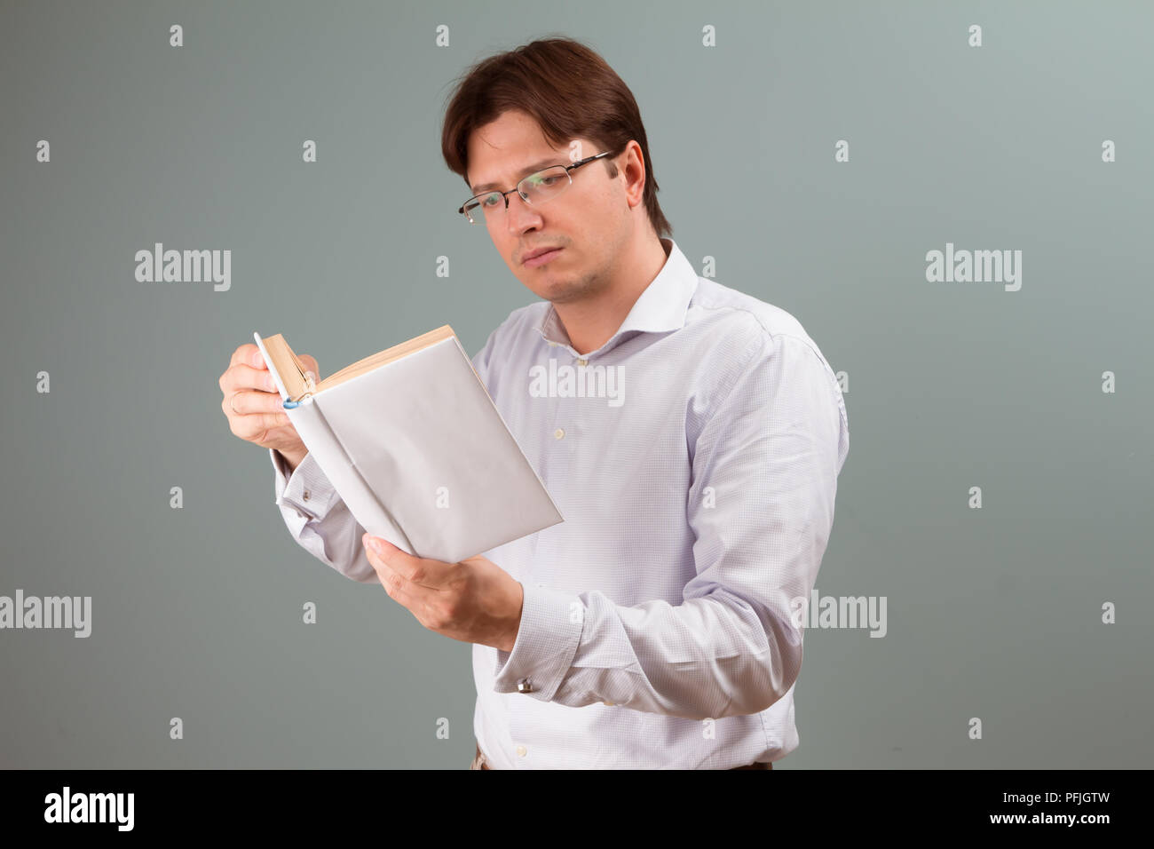 A young man focused on reading a book in white cover; horizontal orientation studio portrait. - Stock Image