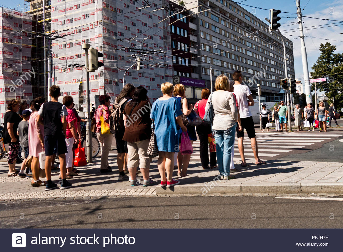 group of people standing at a crosswalk waiting for street light to became green and cross the street - Stock Image