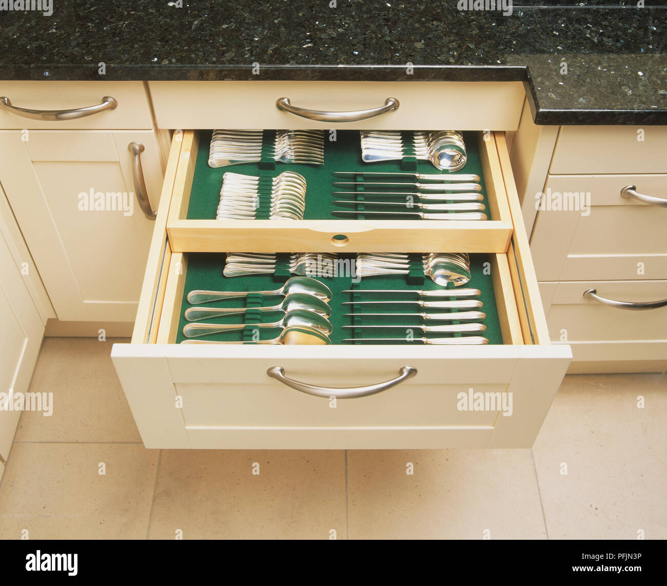 Set Of Silver Cutlery Neatly Stored In Kitchen Cabinet Drawer Close