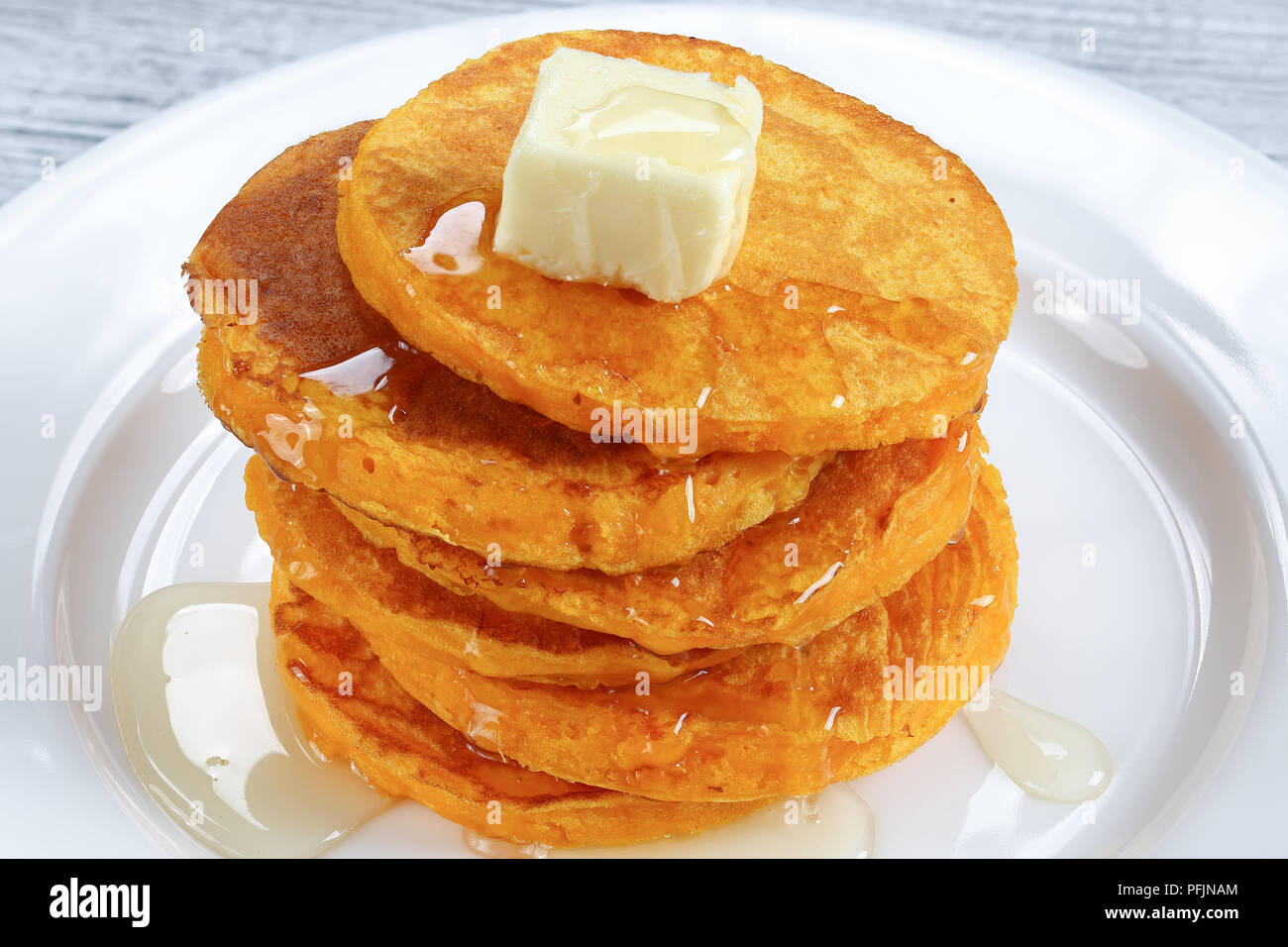 close-up of stack of pumpkin pancakes topped with piece of butter and pour over with honey on white plate on kitchen tablecloth, view from above Stock Photo