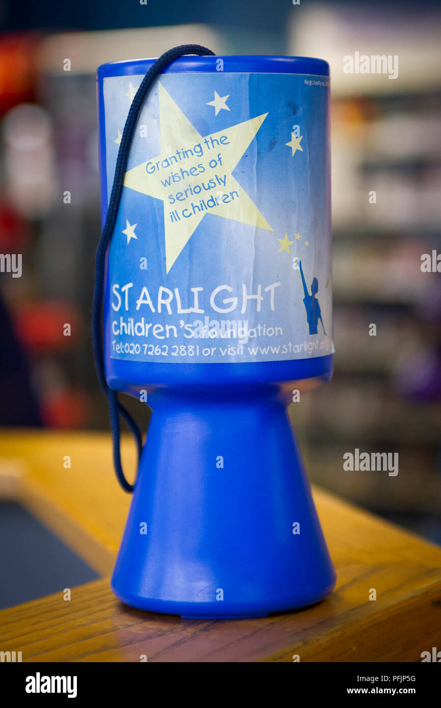 Starlight Charity collection box on a shop counter - Stock Image