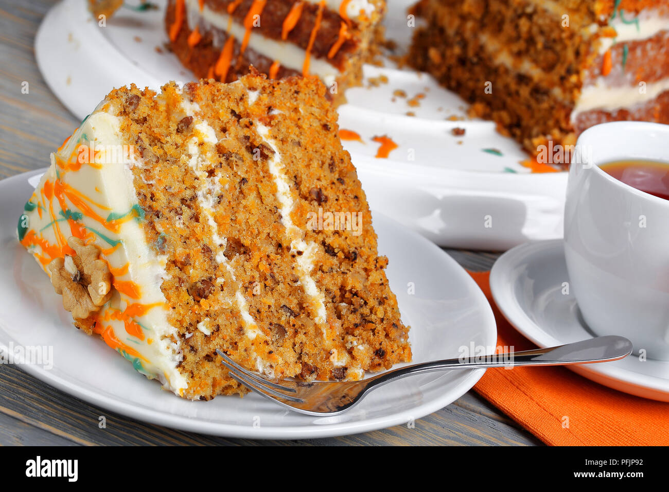 piece of classic carrot cake with cream cheese frosting decorated with walnuts and drizzled with colorful ganache with cup of tea on wooden table, vie - Stock Image