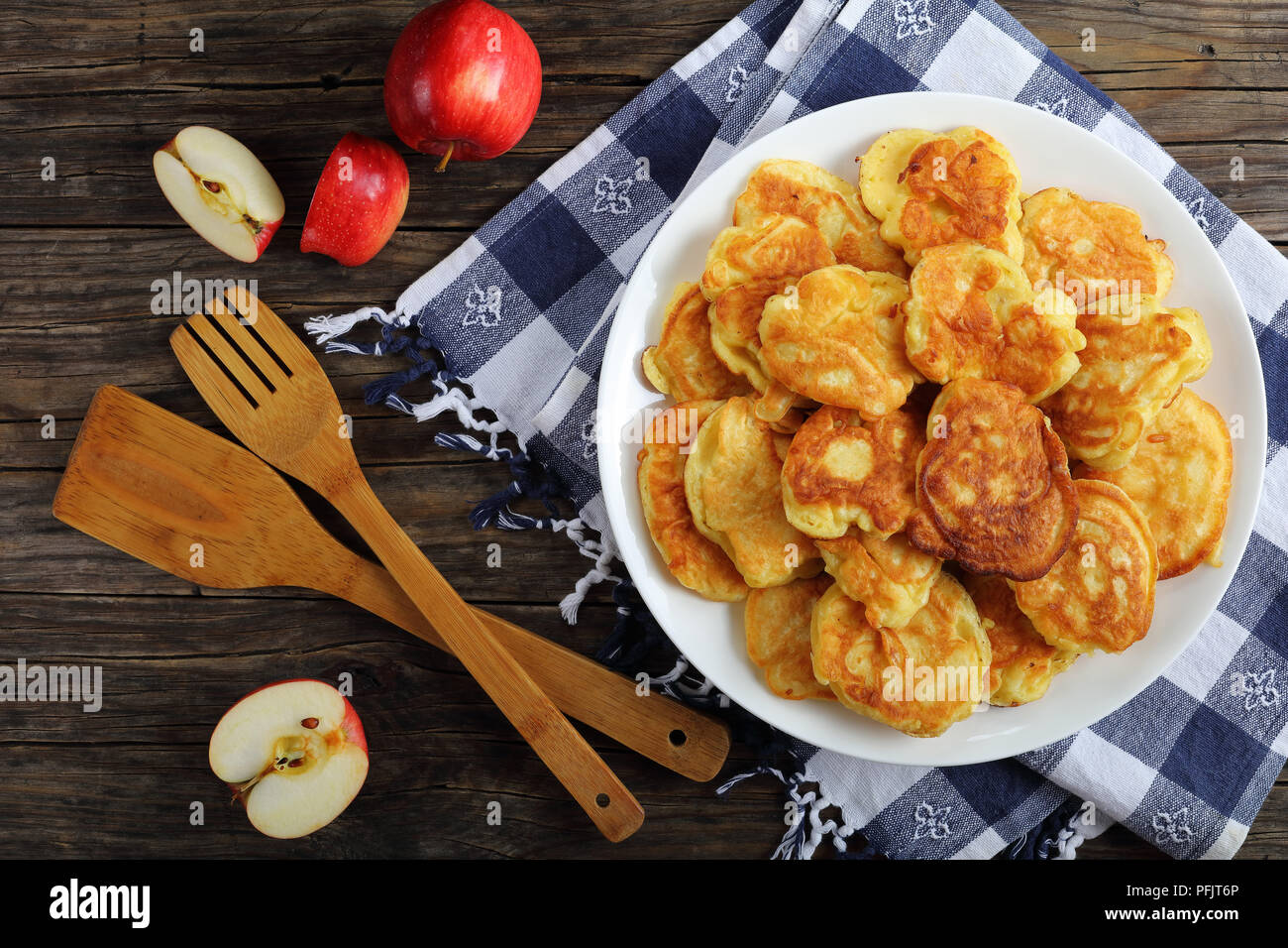 delicious Apple Greek Yogurt Pancakes - thick, fluffy and loaded with juicy pieces of fruits, on white plate on old dark wooden table with spatulas an - Stock Image