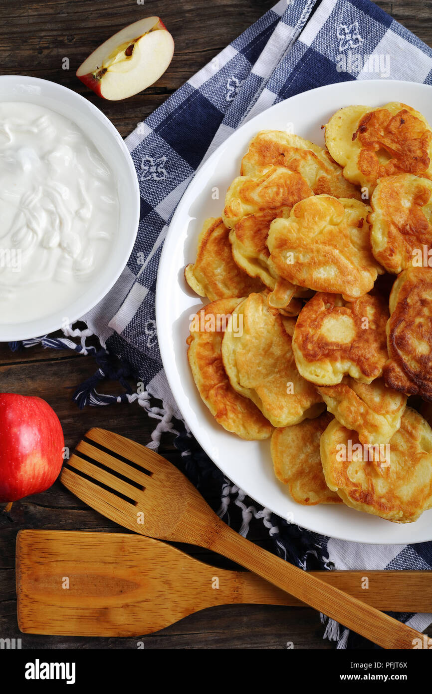 delicious Pancakes loaded with juicy pieces of apple, on white plate on old dark wooden table with sour cream in bowl and apples at background, vertic Stock Photo