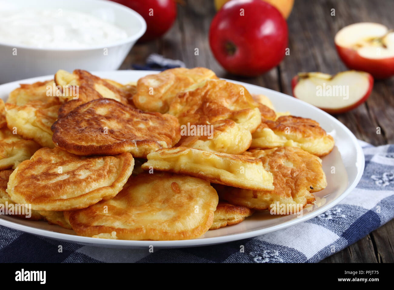 tasty fluffy Pancakes loaded with juicy pieces of apple, on white plate on old dark wooden table with sour cream in bowl and apples at background, sid - Stock Image