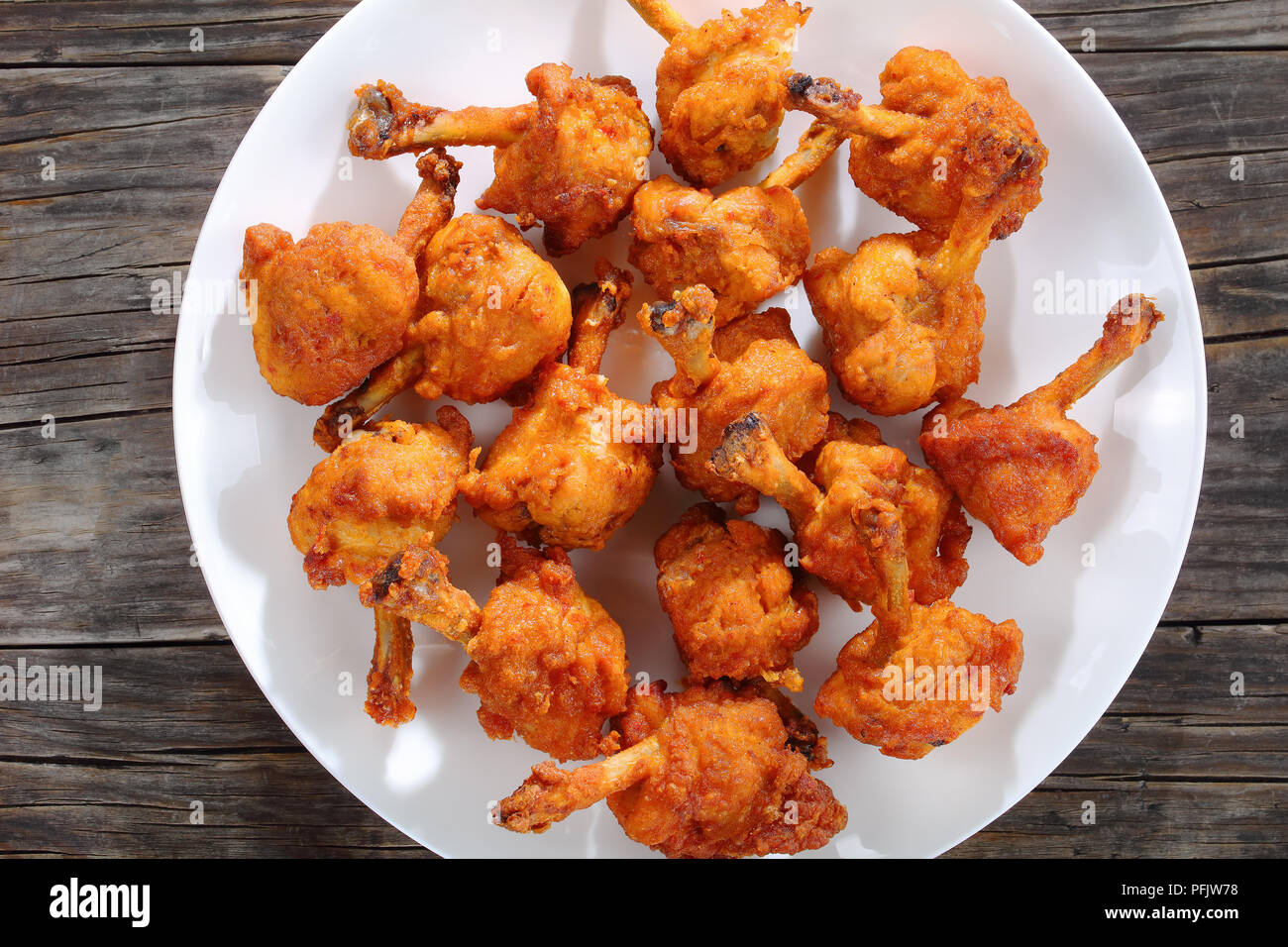 delicious deep fried battered crispy chicken winglets on a white plate on dark wooden table, horizontal view from above - Stock Image