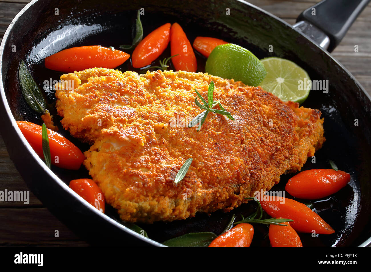 fried breaded white fish steak with glazed carrots, cut into tourne (oval shape), fresh lime slices, sage and rosemary in skillet on wooden table, vie - Stock Image