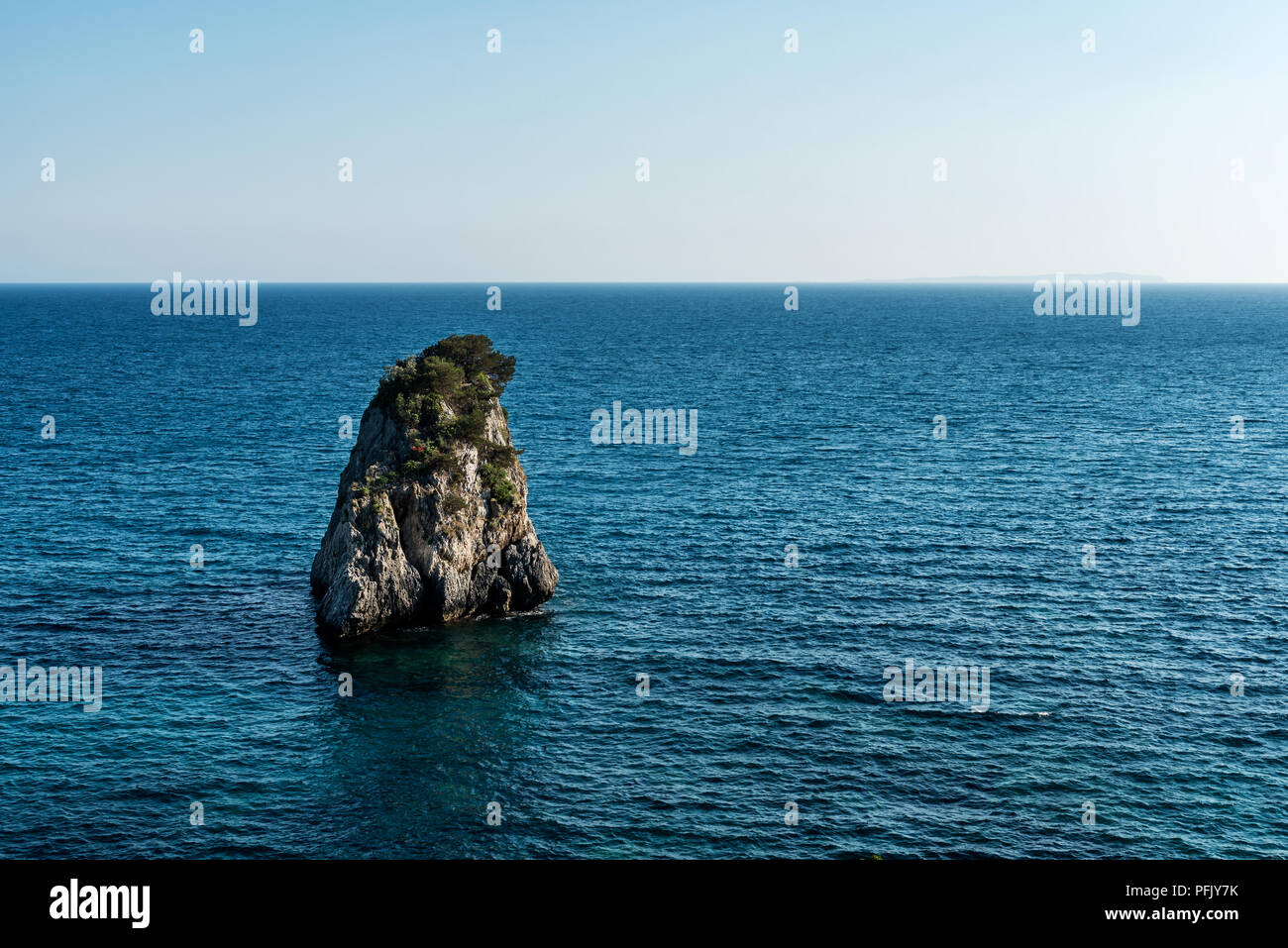 Lonely inhospitable uninhabited island in blue Ionian Sea in Greece - Stock Image