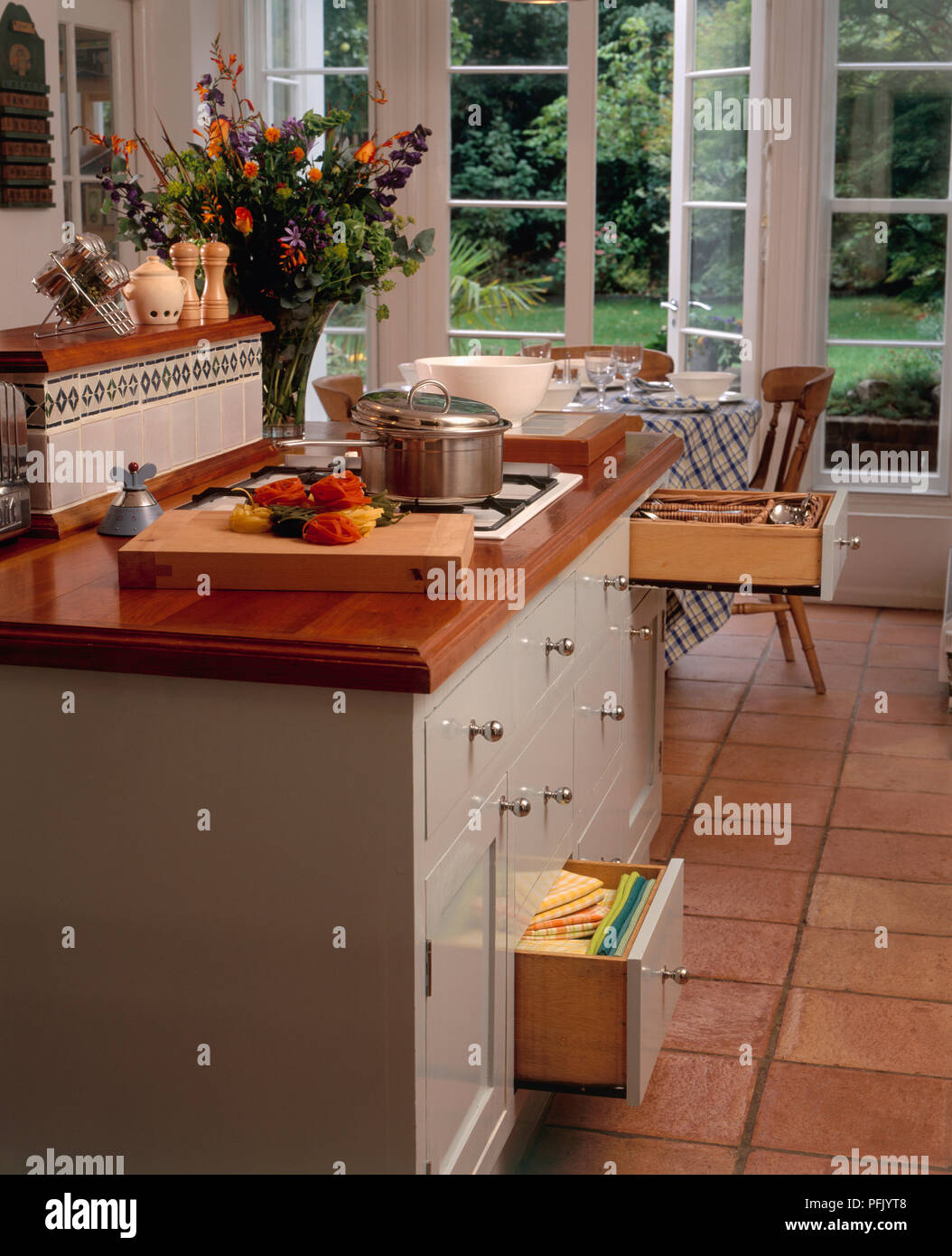 Kitchen in white and brown tones, with terracotta tiled floor, drawer unit underneath hob, and dining table with door open onto garden - Stock Image