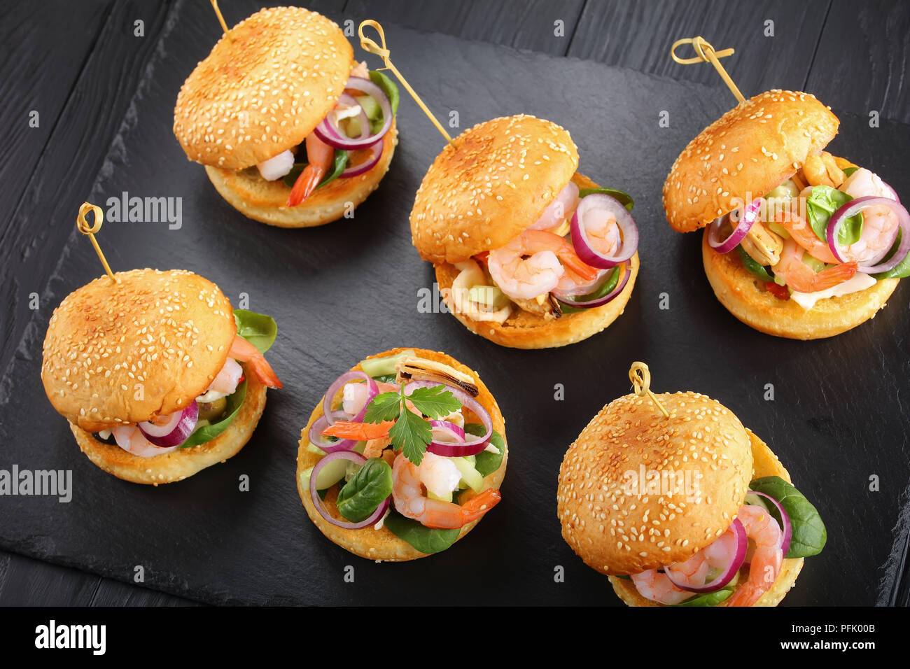 delicious small burgers pinned with bamboo skewers or pinchos with shrimps, calamari, mussels, red onion rings and finely chopped cucumber, spain cuis - Stock Image