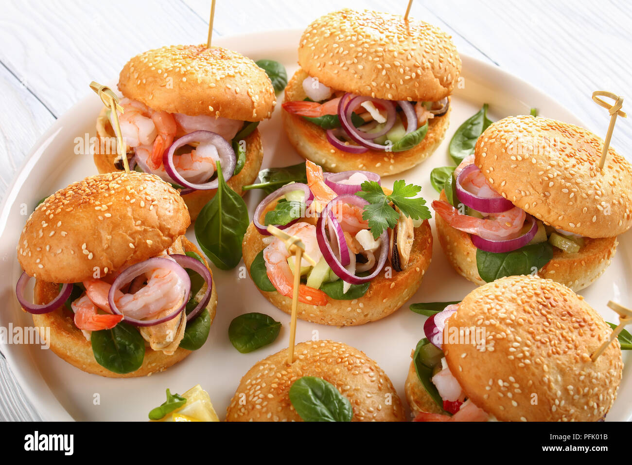 delicious grilled juicy burgers pinned with bamboo skewers or pinchos with seafood, red onion and greens on white platter on wooden table, spain cuisi - Stock Image