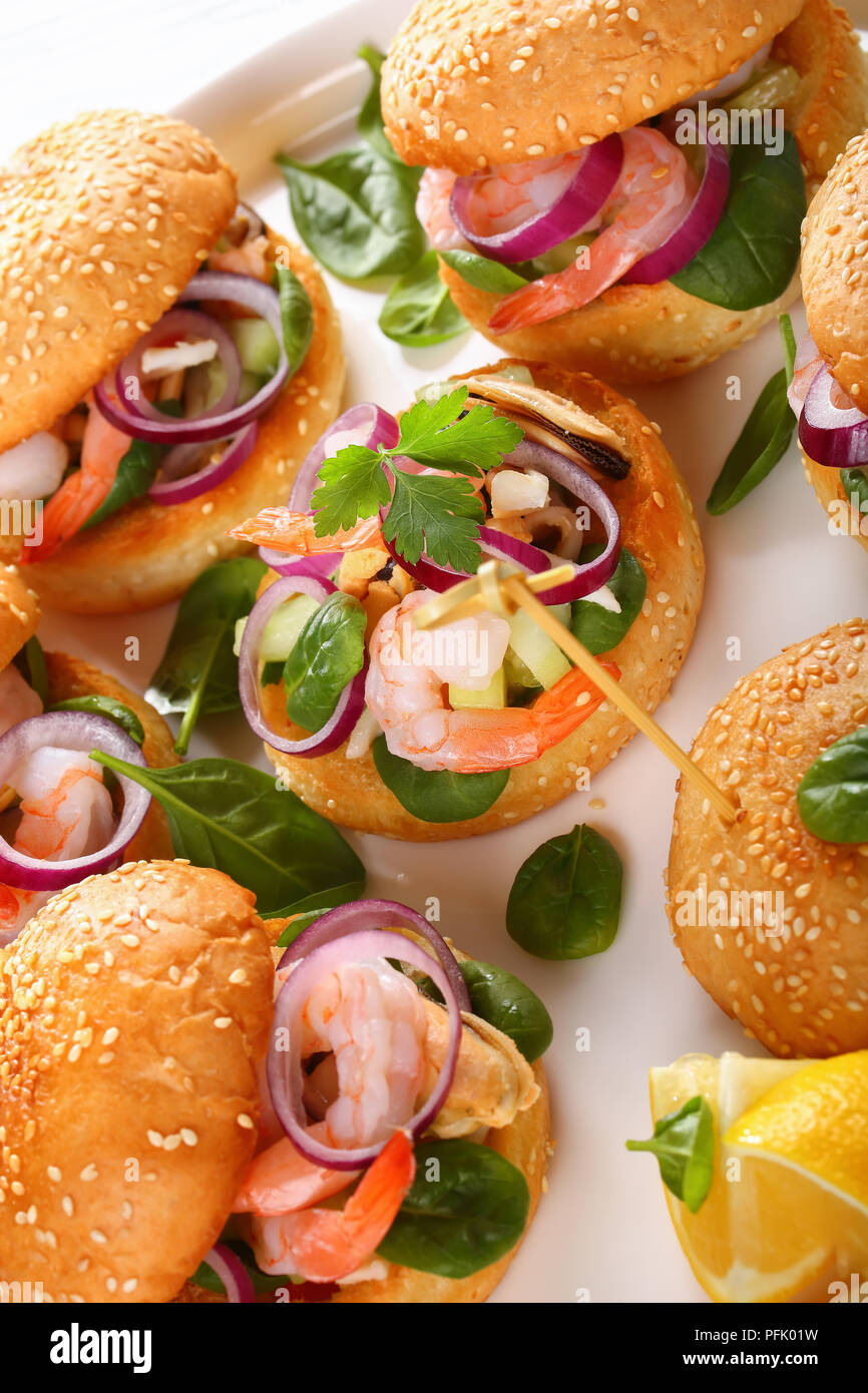 grilled juicy burgers pinned with bamboo skewers or pinchos with seafood - shrimps, mussels, squid strips, red onion and spinach on white dish on wood - Stock Image