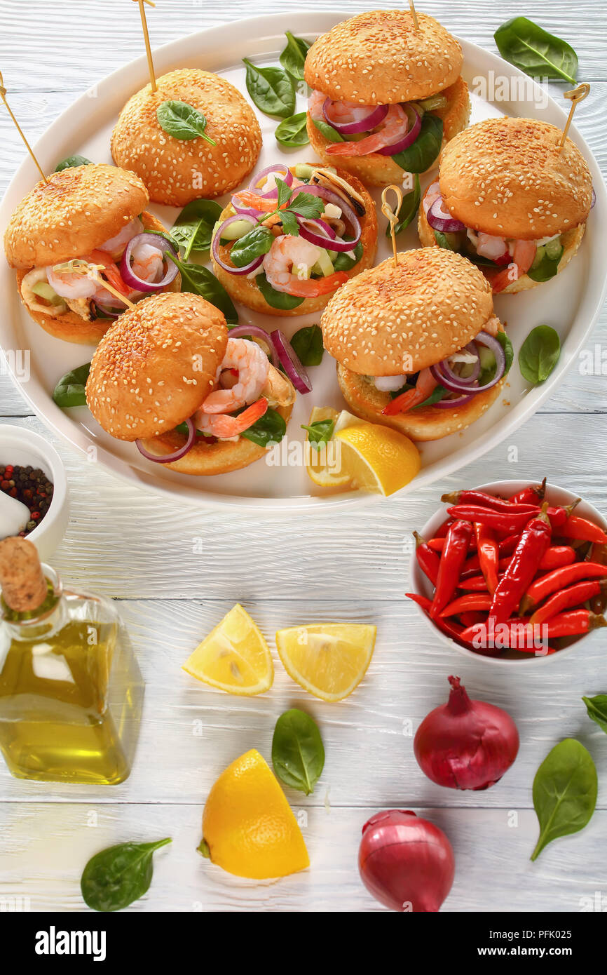 grilled juicy burgesr pinned with bamboo skewers or pinchos with seafood - shrimps, mussels, squid strips, red onion and spinach on white dish, spain  - Stock Image