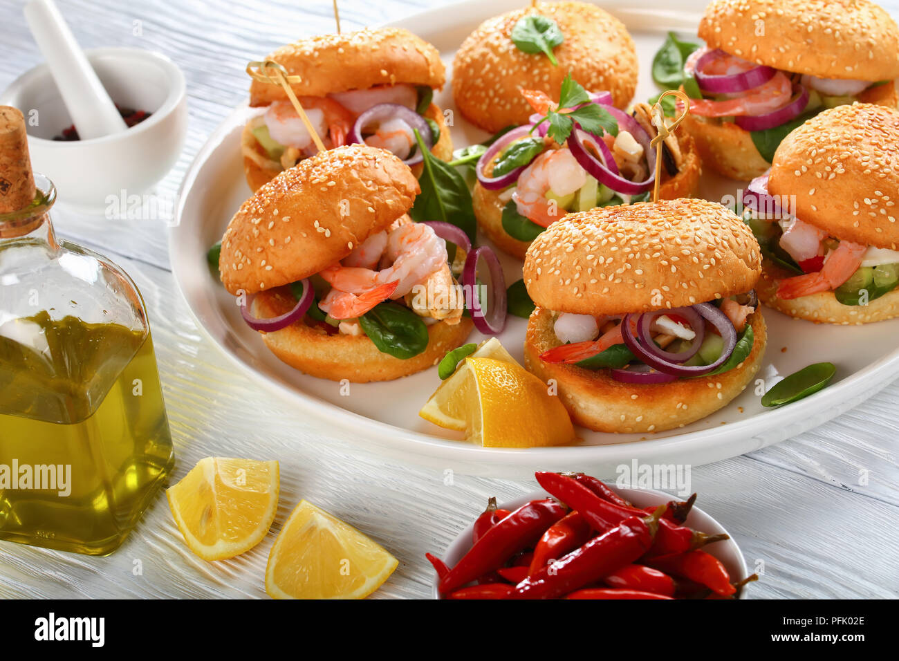 grilled juicy burgers pinned with bamboo skewers or pinchos with seafood - shrimps, mussels, squid strips, red onion and spinach on white dish, spain  - Stock Image