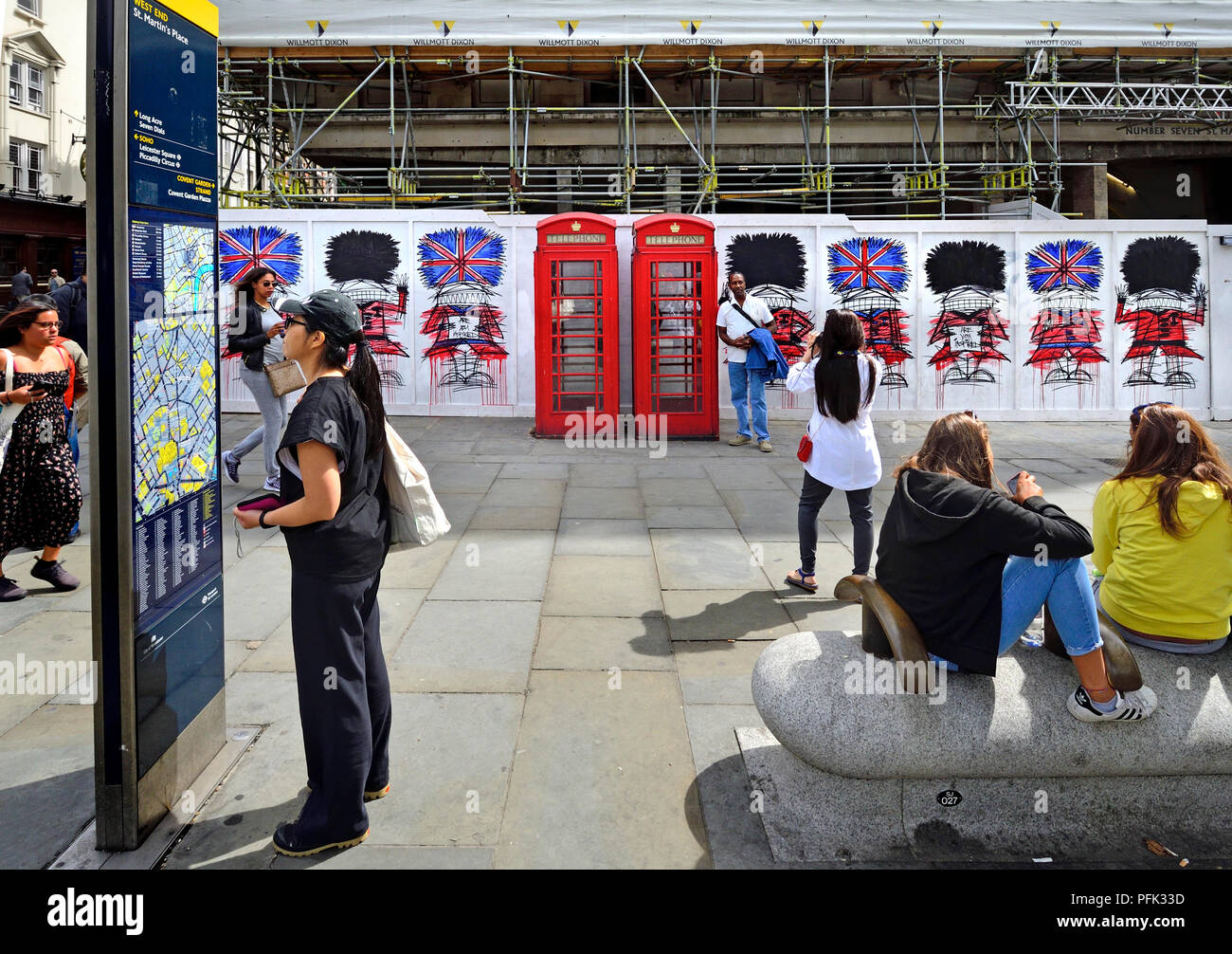Tourists in St Martin's Place, London, England, UK. Traditional red telephone boxes and graffiti guardsmen by artist Nathan Bowendecorating constructi - Stock Image