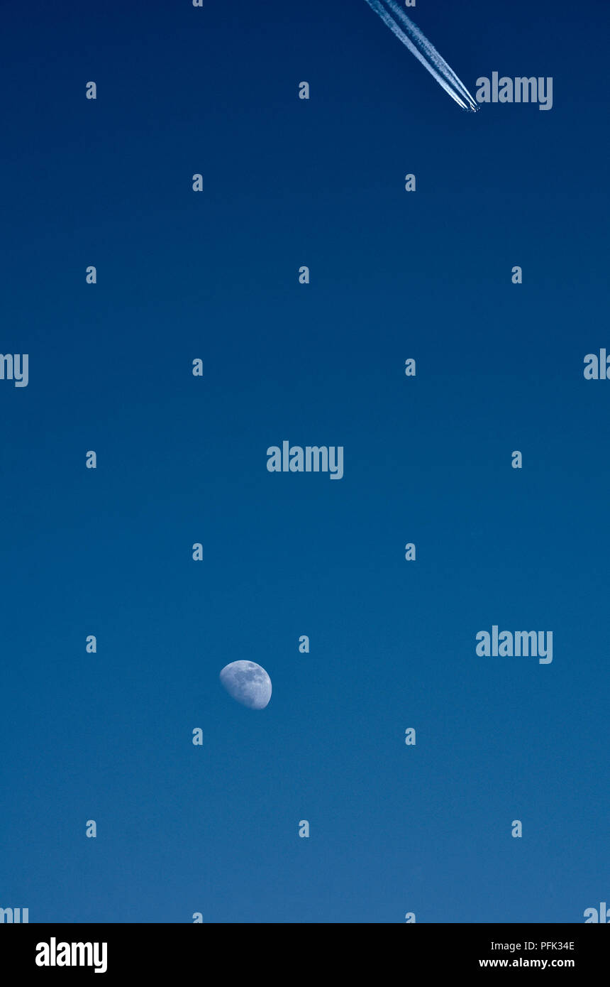 The moon - three quarter phase, early evening before dark. Jet aircraft with vapour trail - Stock Image