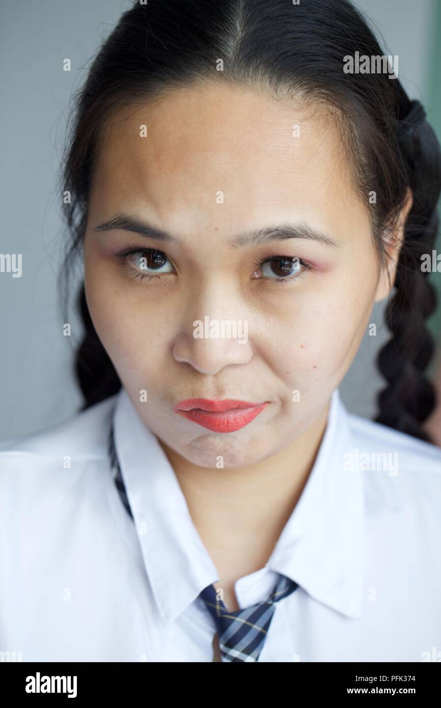 Oriental schoolgirl looking disappointed - Stock Image