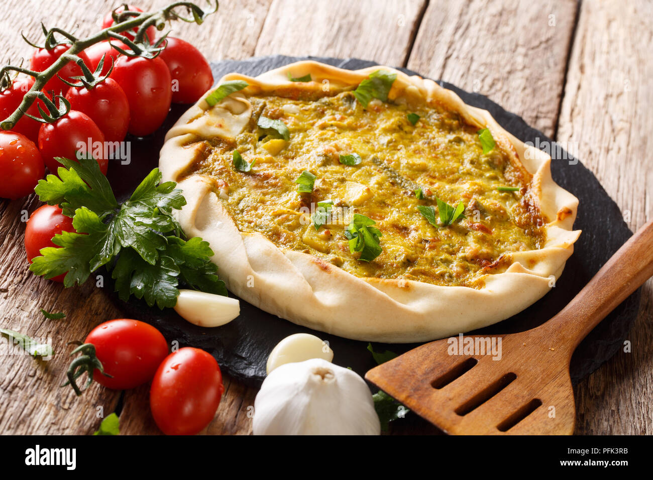 Spicy potato savory tart with vegetables and herbs close up on the table and ingredients. horizontal - Stock Image
