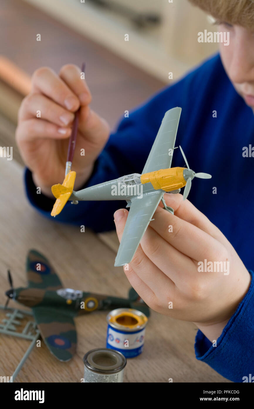 Boy painting model airplane yellow, close-up Stock Photo