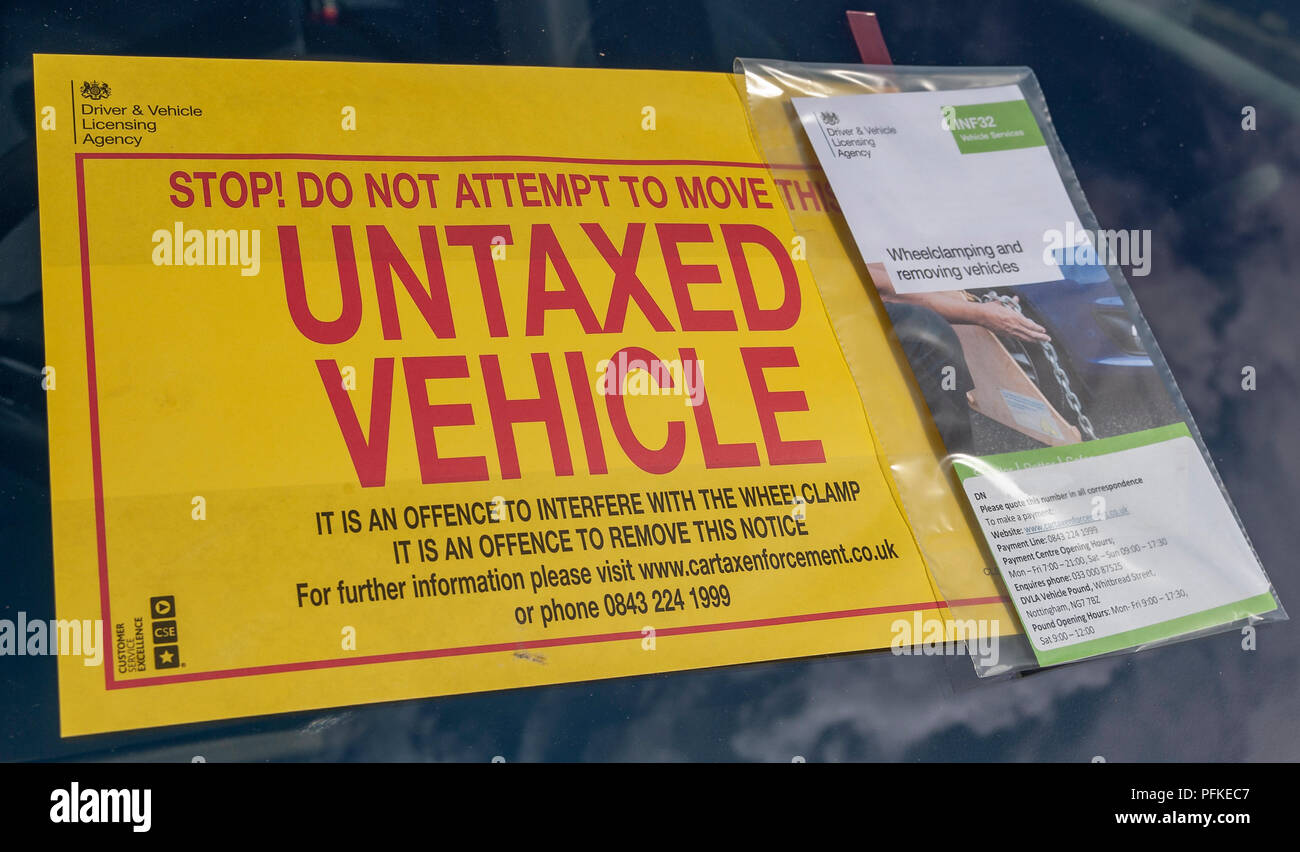A Untaxed Vehicle notice stuck on the windscreen of an untaxed car Stock Photo