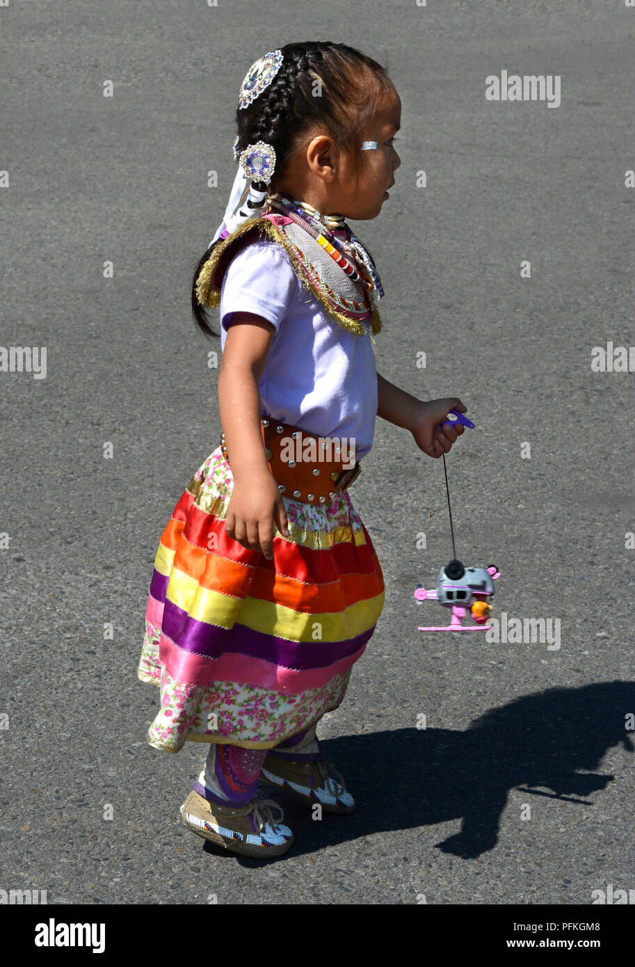 A Native-American child plays with a toy at the Santa Fe Indian Market. - Stock Image