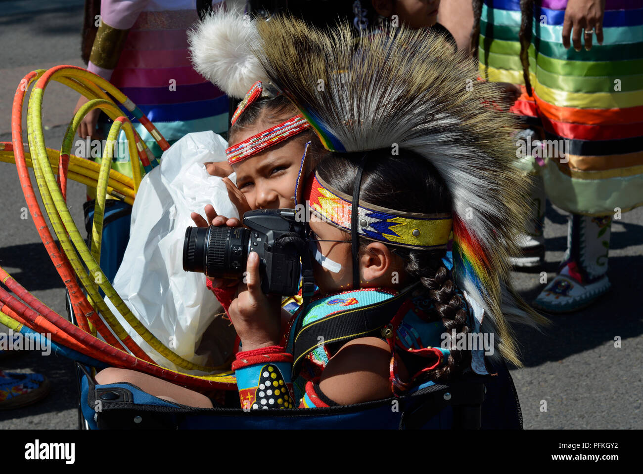 A young Native-American boy wearing traditionall Plains Indian regalia takes a picture with his Nikon camera. - Stock Image