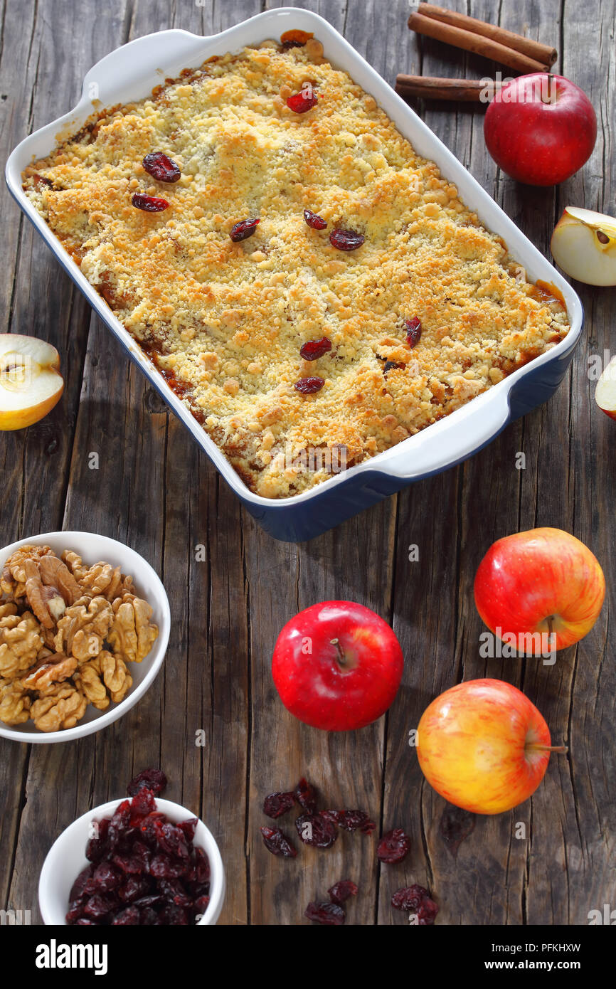delicious apple crumble or apple crisp in baking dish with ingredients on dark wooden table, vertical view from above - Stock Image