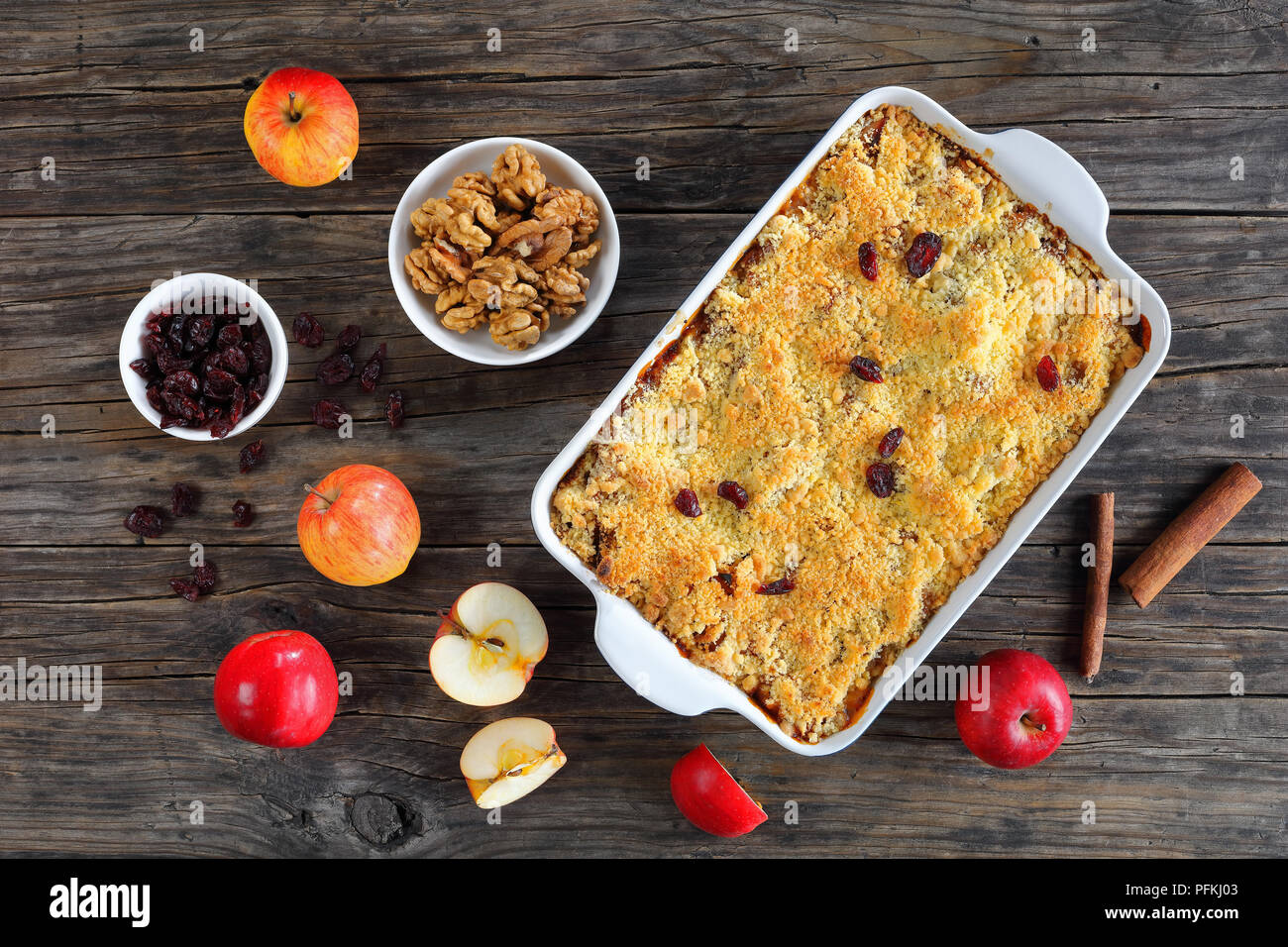 homemade apple crumble or apple crisp in baking dish - dessert consisting of baked chopped apples, topped with a crisp streusel crust, horizontal view - Stock Image