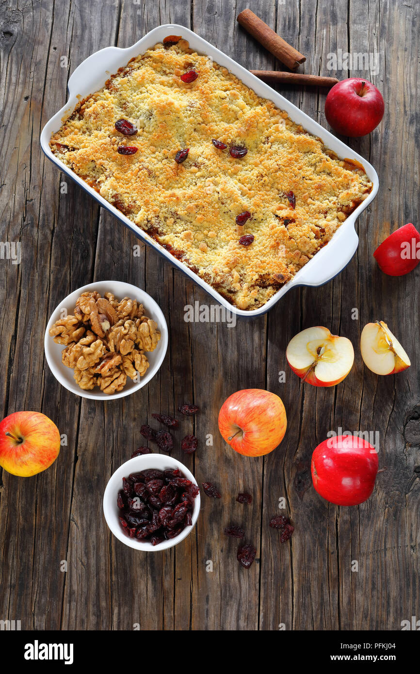 tasty apple crumble or apple crisp in baking dish - dessert consisting of baked chopped apples, topped with a crisp streusel crust, vertical view from - Stock Image
