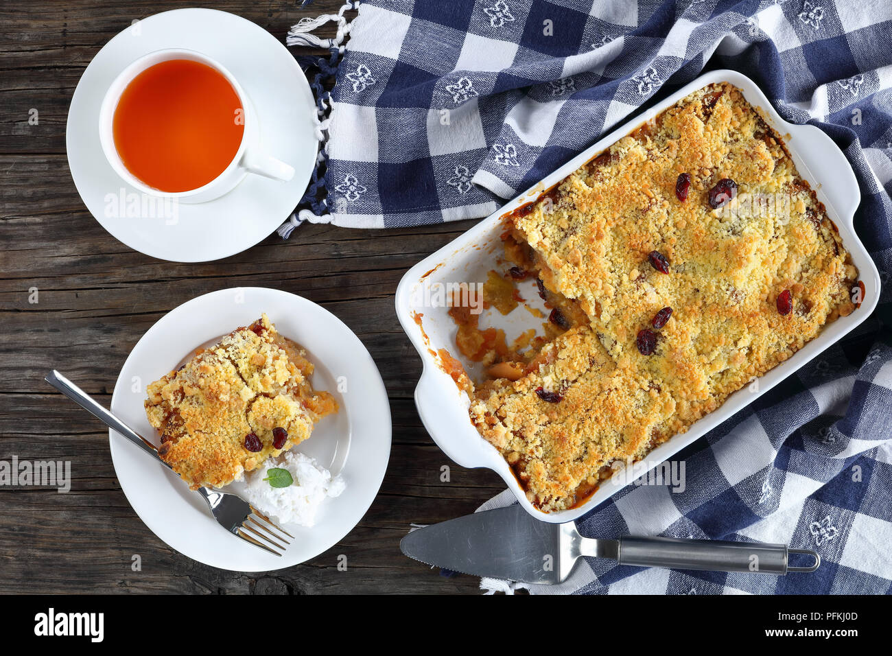 tasty apple crumble or apple crisp in baking dish and a portion on plate with a scoop of coconut milk ice cream. cup of tea at background, view from a - Stock Image