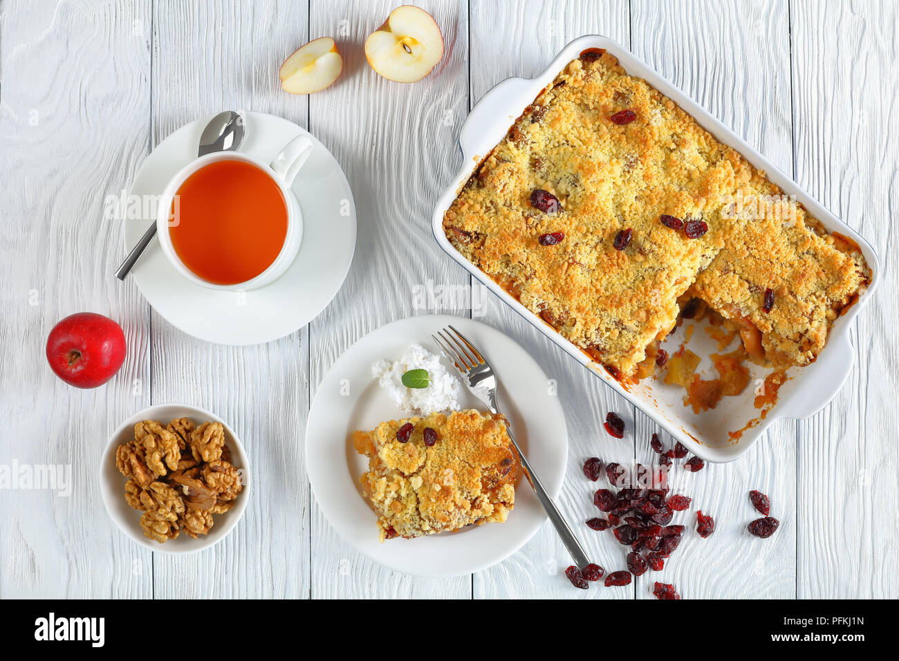 breakfast set -  apple crumble or apple crisp in baking dish and a portion on plate with coconut cream and  cup of tea on table, view from above, clos - Stock Image