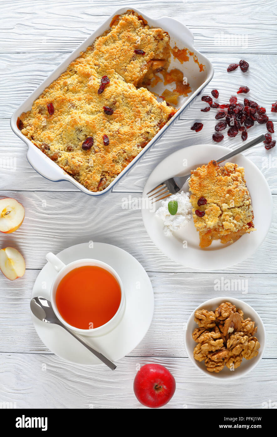 gluten free breakfast set -  apple crumble or apple crisp in baking dish and a portion on plate with coconut cream and  cup of tea on table, vertical  - Stock Image