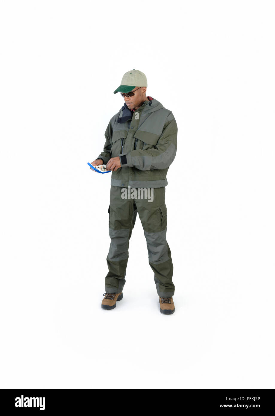 Man dressed for fly fishing, choosing fly from fly box Stock Photo